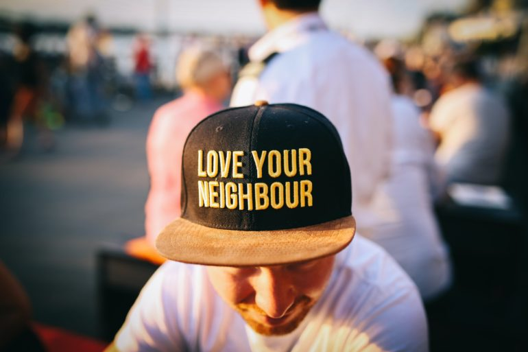 "Man wearing ""love your neighbour"" hat"