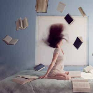 Woman sitting on bed with flying books