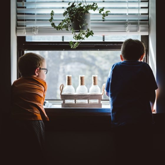 Two children looking out a window