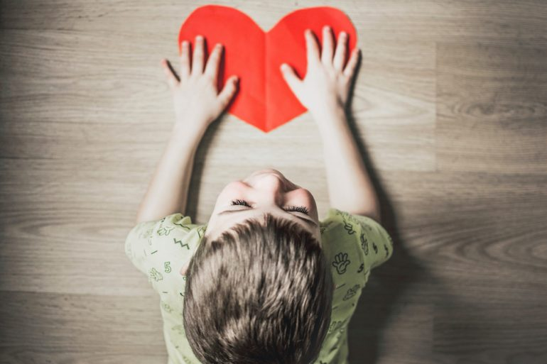 Child with heart shaped paper