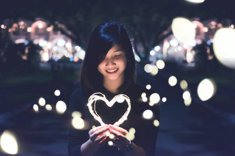Girl holding heart shaped light