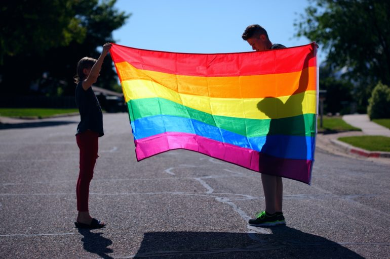 Woman and child holding rainbow flag