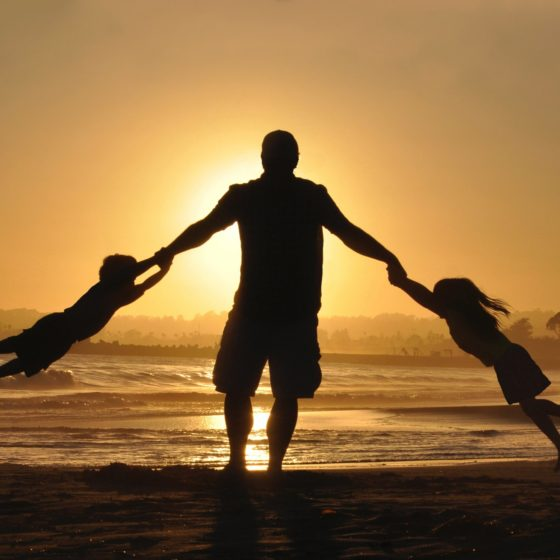 Father with children at sunset