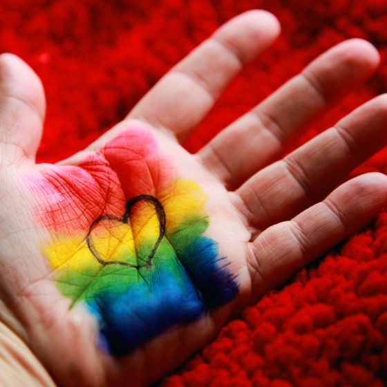 Rainbow and heart painted on a hand