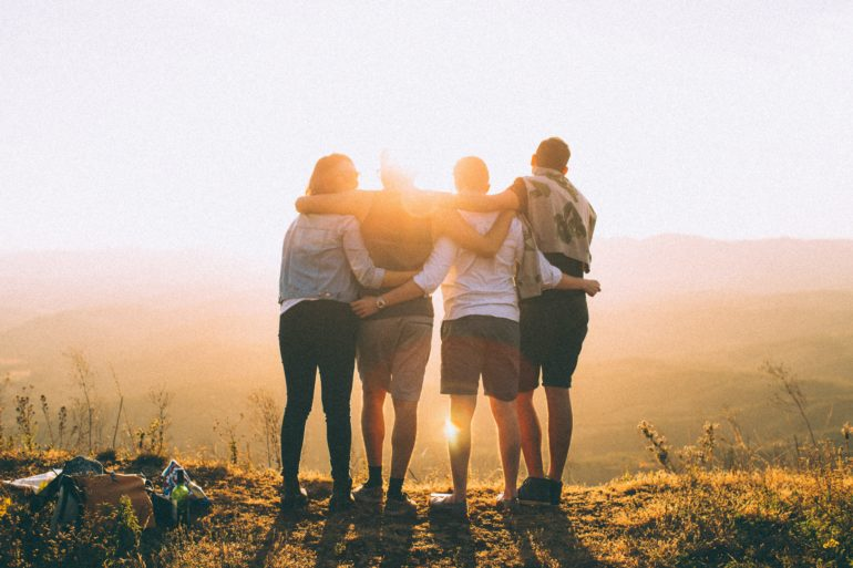 Friends hugging at sunset